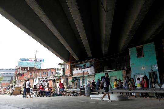 Un grupo de vecinos espera respuestan abajo de la autopista. Foto: LA NACION / Maxie Amena
