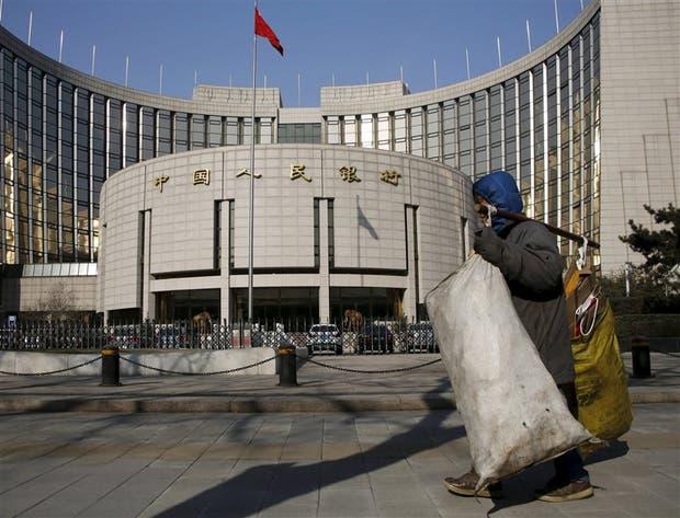 Un recolector de basura pasa frente al Banco del Pueblo Chino, ayer, en Pekín