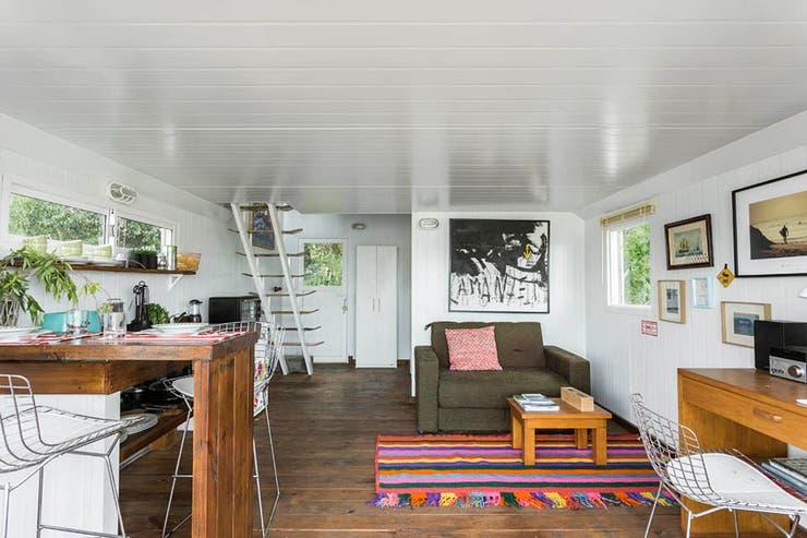 En el living, sillón marrón con mesa baja de madera sobre tapete de colores