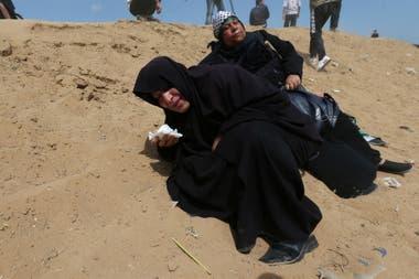 Mujeres palestinas reaccionan al gas lacrimógeno disparado por las tropas israelíes durante la protesta