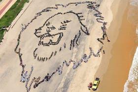 Cientos de niños sudafricanos forman la cabeza de un león como llamada de atención para pedir medidas urgentes para combatir el cambio climático, en Durban