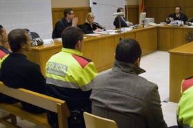 De espaldas, Matías Miret y Gustavo Julia, vigilados por tres policías, frente a los jueces