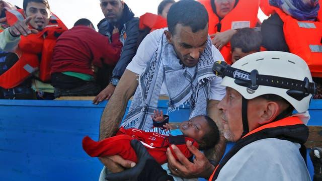 Un bebe es rescatado con vida, durante una operación de rescate en el centro del Mediterráneo en aguas internacionales a unos 15 millas náuticas frente a la costa de Zawiya en Libia
