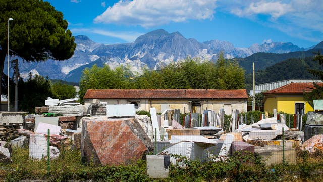 Un negocio de venta de mármol con los Alpes Apuanos de fondo en Carrara