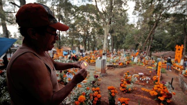 Un hombre prende velas en un cementerio de Tzintzuntzan
