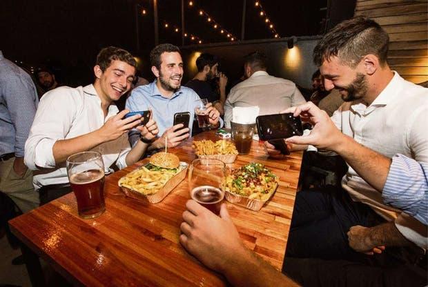 Un grupo de amigos cumple con el ritual de sacarles la foto a los platos antes de empezar a comer