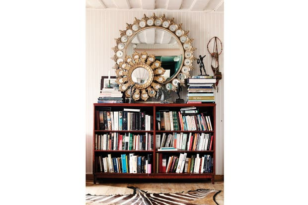 Un rincón para los libros en la biblioteca de madera sobre la que resplandece un dorado dúo de espejos de una extinta tienda sueca..