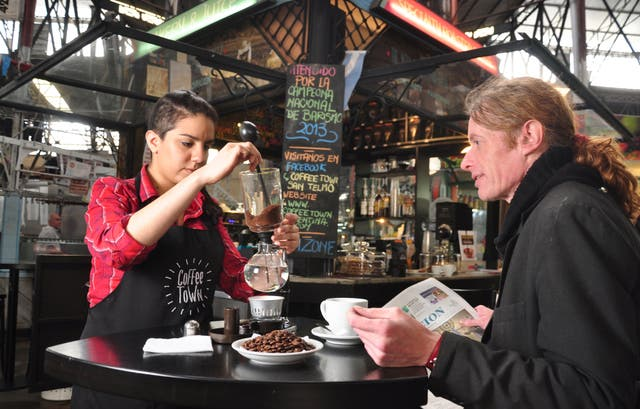 En Coffee Town, Tony Trainor prueba el café Kona, de Hawai, preparado por la barista Agustina Román con una cafetera de vacío