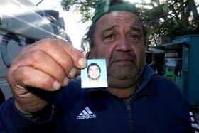 El padre Miguel Ramírez muestra una foto de hijo, que murió luego de recibir el impacto de una bengala en un recital de La Renga