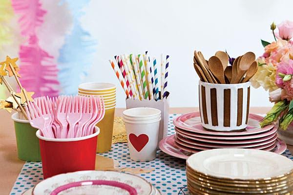 Platos antiguos (Salmón, desde $75), cucharas de madera ($10 cada una, se consiguen en Cualquier Bazar), cubiertos de plástico rosa (Ticoral, $14 el pack) y vasos de corazones (Stu, $95 los 50). Foto: Victoria Schiopetto. Producción de Yamila Bortnik