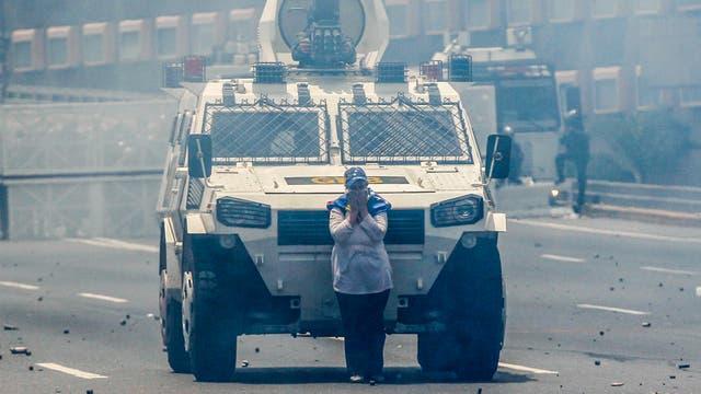 Una manifestante bloqueando uno de los blindados de la Guardia Nacional Bolivariana. Foto: AP / Ariana Cubillos