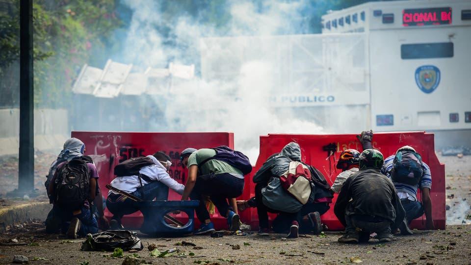 Estudiantes de la Universidad Central de Venezuela se protegen durante las protestas. Foto: AFP / Ronaldo Schemidt