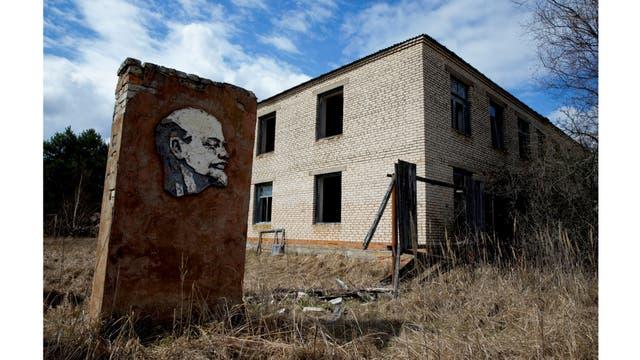 Un panel con un retrato de Lenin y un edificio abandonado se ven en la zona de exclusión de 30 km alrededor del reactor nuclear de Chernobyl en la aldea abandonada de Orevichi, Bielorrusia
