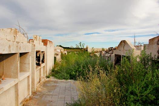 Entre los arbustos se ven los pabellones de nichos que, por la presión del agua, se abrieron y dejaron salir los ataúdes. Foto: LA NACION / Mauricio Giambartolomei