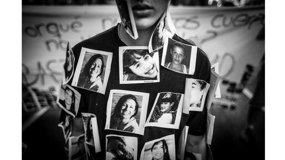 """Un joven realiza una perfomance con fotos de víctimas de violencia de género, durante la marcha """"Ni una menos"""" desde el Congreso Nacional a la Plaza de Mayo. La marcha, en el día Internacional de la Eliminación de la Violencia contra la Mujer, se replicó en distintas ciudades del país, Buenos Aires2. Foto: Zabala Martín"""