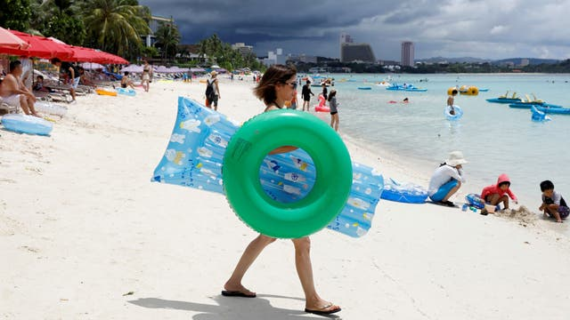 Turistas disfrutando del mar en Tumon, un distrito turístico de la isla de Guam
