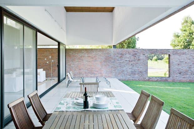 El living exterior se armó con un dúo de poltronas con apoyapiés de diseño italiano con estructura de caño pintada al horno y tejido en PVC (Mausy Design)..
