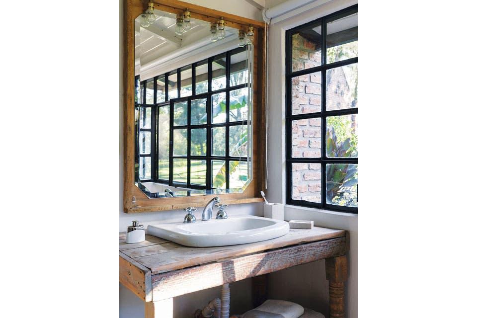 El vanitory de madera rústica con un espejo, armado por Agos con listones sobrantes de la obra y lámparas de su marca.  Foto:Living /Daniel Karp