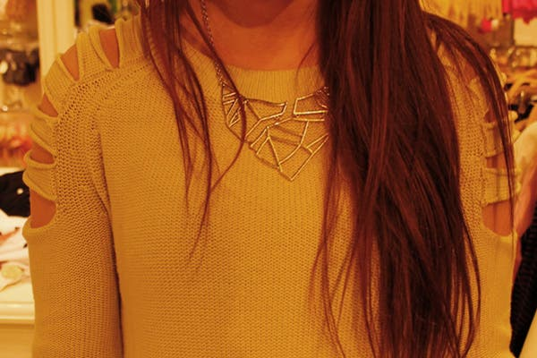 ¡Un pequeño detalle puede levantar cualquier prenda básica! en este caso, un sweater manteca con recortes en los hombros acompañado de un collar de diseño en tonos dorados..