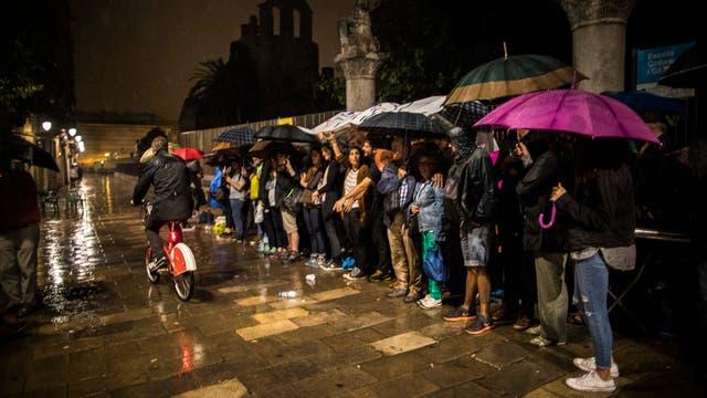 Bajo la lluvia, un grupo de personas hace fila frente a un centro de votación, en Barcelona
