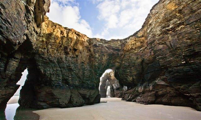 La palya de Las Catedrales, en un extremo de Galicia, es conocida por grandes arcos cavados en las rocas por el mar a lo largo de millones de años