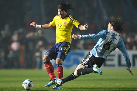 Dayro Moreno cubre la pelota mientras Milito intenta llegar al balón. Foto: AFP