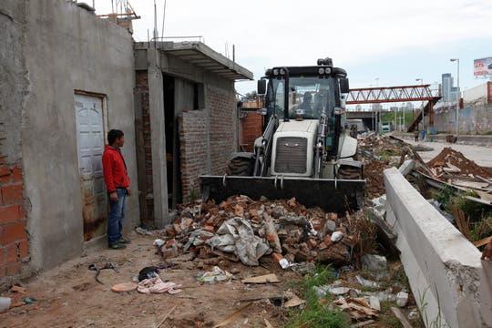 Los que se resisten a abandonar sus casas observan como las topadoras recogen los escombros. Foto: LA NACION / Maxie Amena