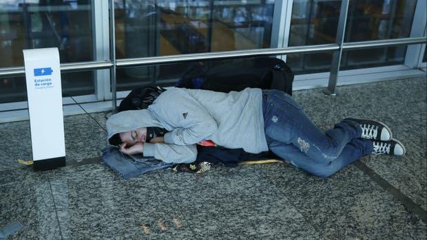 Un pasajero duerme incómodo en el suelo