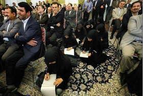 Mujeres sentadas tomando nota, mientras todos los hombres están ocupando sillas