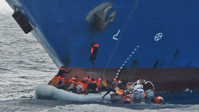 Inmigrantes en un semi rígido de la ONG Migrant Offshore Aid Station, con sede en Malta, son ayudados a subir al barco Tuna 1, Después de que unos 20 inmigrantes en otra embarcación de goma se ahogaran en el Mediterráneo