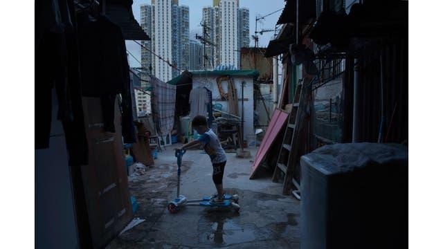 Un niño de cinco años juega fuera de su pequeña casa hecha de hormigón y de chapa en la terraza de un bloque de departamentos.