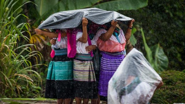 Mujeres se cubren de la lluvia mientras esperan la llegada de María de Jesús Patricio al acto de campaña en el bastión zapatista de Morelia en el estado sureño de Chiapas