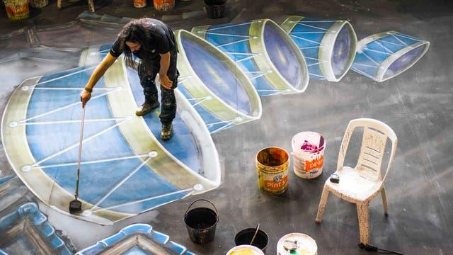 Un pintor crea un telón de fondo escénico para la producción del ballet El Cascanueces en un taller dentro del Auditorio Adela Reta en Montevideo