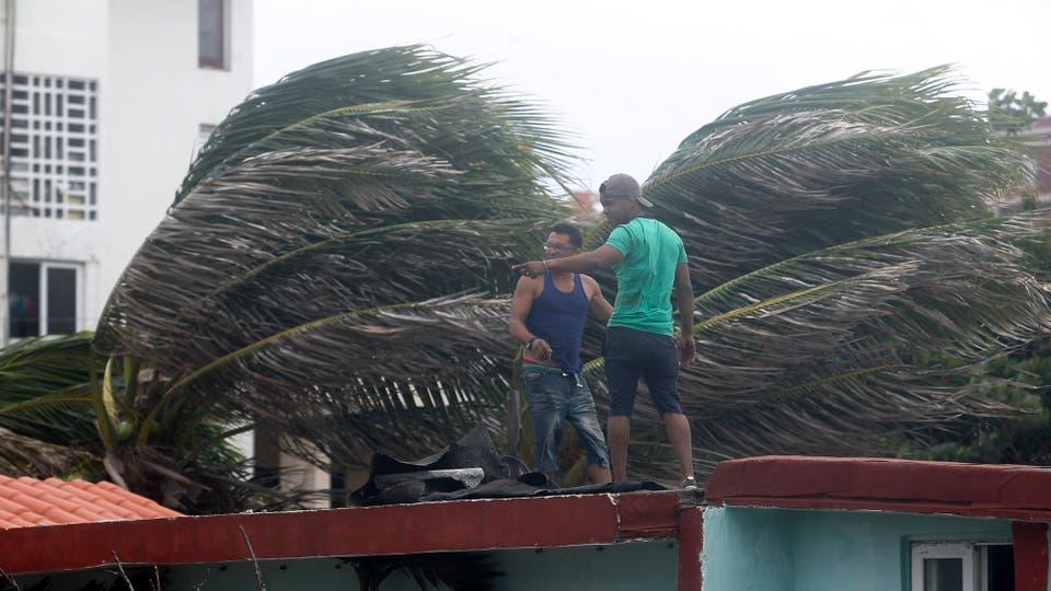 Dos hombres aseguran elementos en el techo de una vivienda. Foto: EFE / Alejandro Ernesto