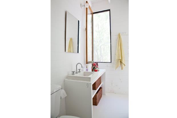 Una puerta corrediza comunica con el baño privado con ventana y ducha; los muebles de guardado realizados en madera son parte de la estructura fija..
