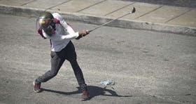 Un manifestante con un palo de golf