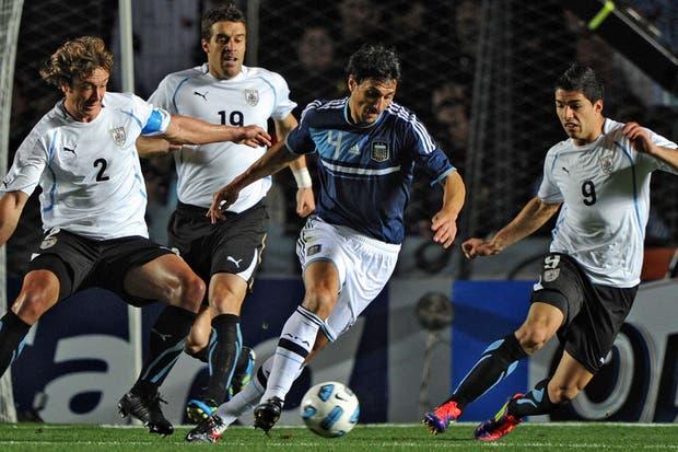 Burdisso escapa de tres jugadores de Uruguay.  Foto:lanacion.com /Fabián Marelli