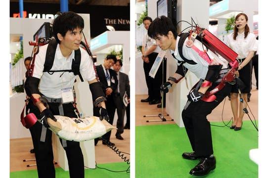 Estudiantes de la universidad de Tokio muestran un exoesqueleto que les permite cargar objetos pesados sin peligro físico. Foto: AFP