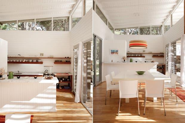 La cocina integrada mediante una barra de machimbre con tapa en mármol de Carrara, a tono con la mesada del mismo material. La mesa de comedor cuadrada fue diseñada por el estudio Martín Gómez Arquitectos..