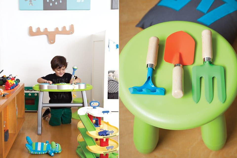 Sobre un banquito verde (Ikea), juego de jardinería (Easy). Vicente juega con un teclado didáctico (Imaginarium) bajo un perchero de alce color madera (Fabrikken).  /Magalí Saberian