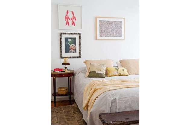 . En el cuarto principal, cama vestida con almohadones pintados (Good Luck Casa) y mesita de la abuela de Roby con un velador alemán antiguo comprado en la feria paraguaya de San Bernardino. El toque rústico está dado por la alfombra en cuero crudo bordado (Allá ité) y el banco de madera.  /Pompi Gutnisky