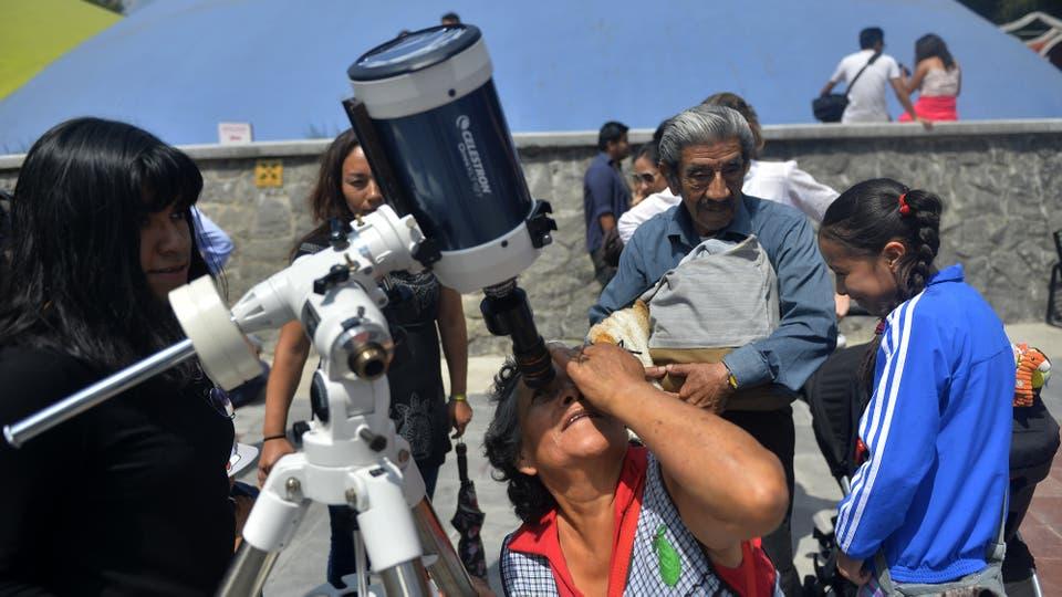 Una mujer mexicana mira a través de un telescopio al comienzo del eclipse solar, en la explanada del Museo de Historia Natural de la Ciudad de México, en donde también se pude ver el eclipse. Foto: Reuters