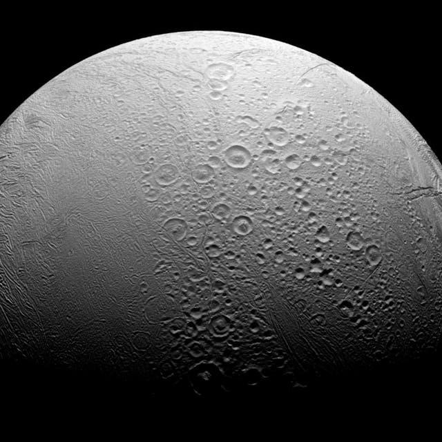 Encélado, uno de los satelites de Saturno, es un mundo dividido. Al norte, vemos cantidades copiosas de cráteres y evidencia de los muchos impactos que la luna ha sufrido en su historia. Sin embargo, al sur vemos un cuerpo más liso con arrugas debido a la actividad geológica.