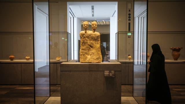 """Una mujer junto a la """"Estatua monumental con dos cabezas"""" de Jordania hacia el año 6500 a.C."""