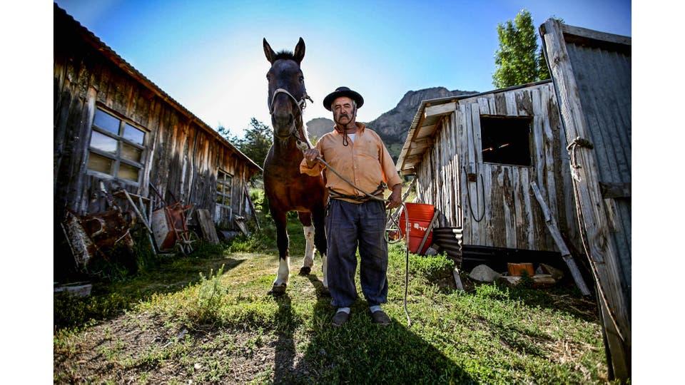 Don Rodolfo Guerra, antiguo habitante de El Chalen, junto a uno de los caballos que utilizaba para el acarreo de material de los escaladores. Foto: LA NACION / Emiliano Lasalvia