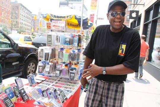 Y miren lo que yo tengo. Un vendedor ambulante muestra todas sus fundas disponibles para el iPhone, cerca de un local de Apple. Foto: AP