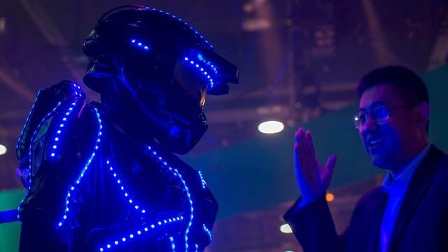 """Una persona vestida de """"glowbot"""" atrae a la gente al stand de Hisense"""