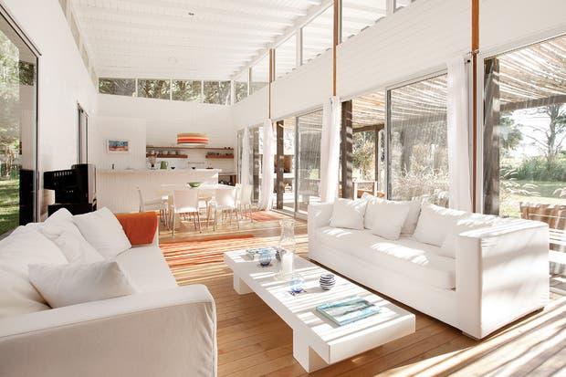 El living, armado con dos amplios sillones tapizados en lino blanco y una mesa ratona que es una adaptación del diseño de la de comedor (todo de Martín Gómez Arquitectos)..