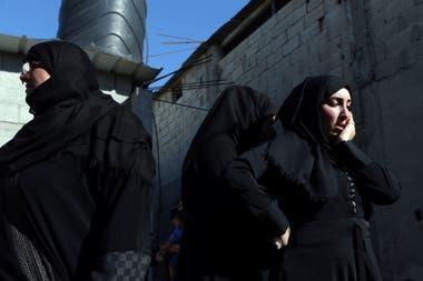 Parientes de un palestino, que murió durante la protesta en la frontera entre Israel y Gaza, llora durante su funeral en Khan Younis en el sur de la Franja de Gaza el 14 de mayo de 2018.
