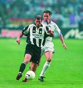 Zidane lleva la pelota; Redondo lo persigue
